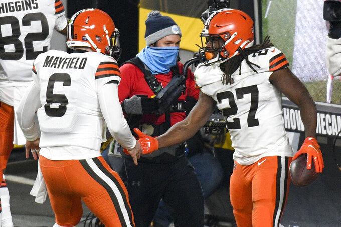 Cleveland Browns running back Kareem Hunt (27) celebrates with quarterback Baker Mayfield (6) after scoring on an eight-yard run during the first half of an NFL wild-card playoff football game against the Pittsburgh Steelers in Pittsburgh, Sunday, Jan. 10, 2021. (AP Photo/Don Wright)