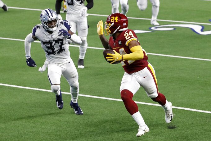 Washington Football Team running back Antonio Gibson (24) gestures with his hand as he gets past Dallas Cowboys safety Donovan Wilson (37) on his way to the end zone for a touchdown in the second half of an NFL football game in Arlington, Texas, Thursday, Nov. 26, 2020. (AP Photo/Roger Steinman)