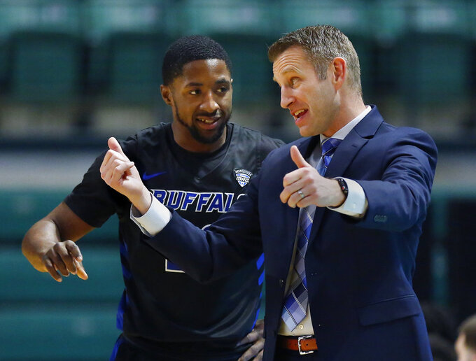 Buffalo coach Nate Oats talks with guard Dontay Caruthers, left, during the first half of the team's NCAA college basketball game against Eastern Michigan on Friday, Jan. 4, 2019, in Ypsilanti, Mich. Buffalo defeated Eastern Michigan 74-58. (AP Photo/Duane Burleson)