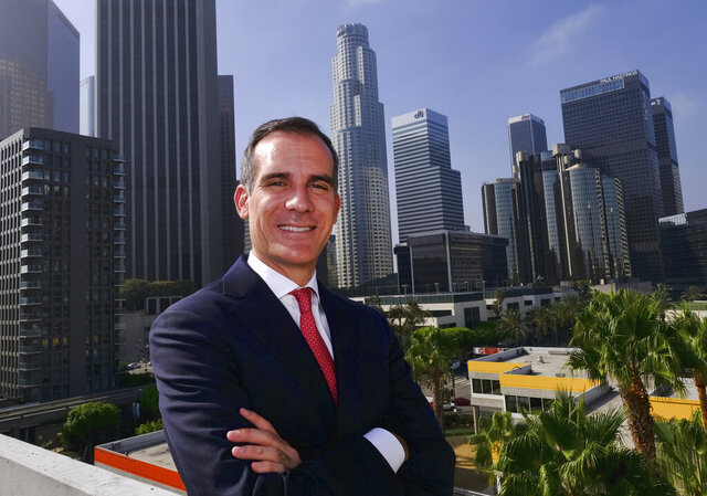 FILE - In this Aug. 23, 2018, file photo, Los Angeles Mayor Eric Garcetti poses in front of a sprawling downtown Los Angeles landscape. Garcetti has taken his name out of consideration for a possible post in the Biden administration. (AP Photo/Richard Vogel, File)
