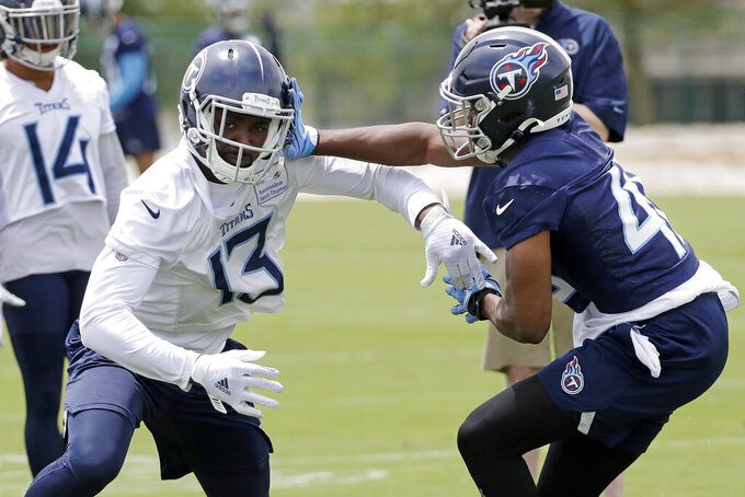 Tennessee Titans wide receiver Taywan Taylor (13) and linebacker LaTroy Lewis (45) run a drill during an organized team activity at the team's NFL football training facility Tuesday, June 11, 2019, in Nashville, Tenn. (AP Photo/Mark Humphrey)