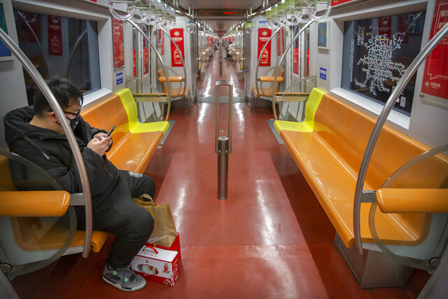 A man wearing a face mask rides a nearly empty subway train in Beijing, Sunday, Jan. 26, 2020. The new virus accelerated its spread in China, and the U.S. Consulate in the epicenter of the outbreak, the central city of Wuhan, announced Sunday it will evacuate its personnel and some private citizens aboard a charter flight. (AP Photo/Mark Schiefelbein)
