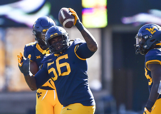 FILE - In this Oct. 17, 2020, file photo, West Virginia defensive lineman Darius Stills (56) reacts after making an interception against Kansas during an NCAA college football game in Morgantown, W.Va. West Virginia had to switch gears quickly to start preparing for Army's triple option offense. The Mountaineers rank 24th defending the run, giving up 126.2 yards, and they're led by All-American lineman Stills. (William Wotring/The Dominion-Post via AP, File)