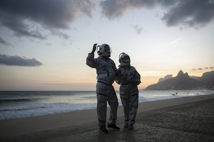 Accountant Tercio Galdino and wife Alicea, dressed in their astronaut costumes, pose for a photo backdropped by Ipanema beach in Rio de Janeiro, Brazil, Saturday, March 20, 2021. The Galdinos have come up with a unique way for protecting themselves and drawing awareness around COVID-19 protective measures – by dressing as astronauts. The pair first began to traverse the iconic beaches fully suited in mid 2020 at the height of the first wave of the pandemic in Brazil, now as cases surge once again they are taking their 'astronaut walks' back to the promenades. (AP Photo/Bruna Prado)