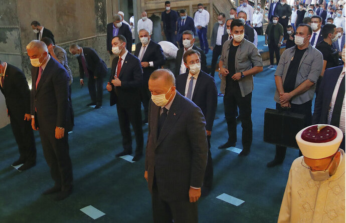 Turkey's President Recep Tayyip Erdogan, front center, takes part in Friday prayers in Hagia Sophia, at the historic Sultanahmet district of Istanbul, Friday, Aug. 7, 2020. Erdogan joined worshipers on July 24 for the first Muslim prayers in 86 years inside the Istanbul landmark that served as one of Christendom's most significant cathedrals, a mosque and a museum before its conversion back into a Muslim place of worship.(Turkish Presidency via AP, Pool)