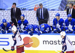 Toronto Maple Leafs coach Sheldon Keefe, back center, and players react as Columbus Blue Jackets centers Boone Jenner (38) and Alexander Wennberg (10) celebrate an empty-net goal during the third period of an NHL hockey playoff game Sunday, Aug. 9, 2020, in Toronto. (Nathan Denette/The Canadian Press via AP)