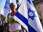 A woman with an Israel flag protests with thousands of people on Sunday, Oct. 13, 2019 in Berlin, Germany, against rising anti-Semitism, days after a man attacked a synagogue in the eastern German city of Halle. More than six thousand participated in the march through the German capital on Sunday. (Paul Zinken/dpa via AP)