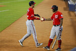 Washington Nationals' Trea Turner, left, is congratulated by Howie Kendrick after scoring on a single by Anthony Rendon during the first inning of a baseball game against the Miami Marlins, Sunday, Sept. 22, 2019, in Miami. (AP Photo/Wilfredo Lee)