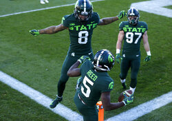 Michigan State's Jayden Reed (5), Jalen Nailor (8) and Tyler Hunt (97) celebrate Reed's touchdown reception against Northwestern during the first half of an NCAA college football game, Saturday, Nov. 28, 2020, in East Lansing, Mich. (AP Photo/Al Goldis)