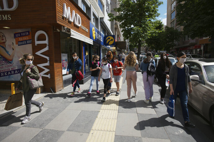 People walk along a popular street, in Ankara, Turkey, Wednesday, June 3, 2020, days after the government lifted a series of restrictions imposed to fight the coronavirus pandemic. People crowded popular streets and parks while restaurants and cafes welcomed sit-in customers and beaches and museums reopened as part of Turkey's broadest easing of coronavirus restrictions. (AP Photo/Burhan Ozbilici)
