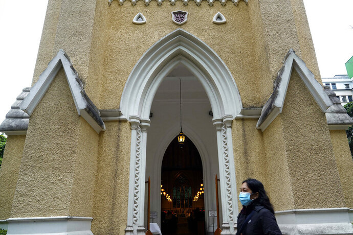 In this Feb. 9, 2020, photo, a church goer wearing a face mask walks past the entrance of St John's Cathedral in Hong Kong. People who troop to churches and chapels were asked to wear protective masks and keep some distance to each other in Hong Kong. (AP Photo/Vincent Yu)