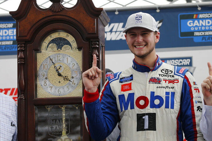 Todd Gilliland poses next to the winners trophy grandfather clock as he celebrates winning the NASCAR Truck Series race at Martinsville Speedway in Martinsville, Va., Saturday, Oct. 26, 2019, (AP Photo/Steve Helber)