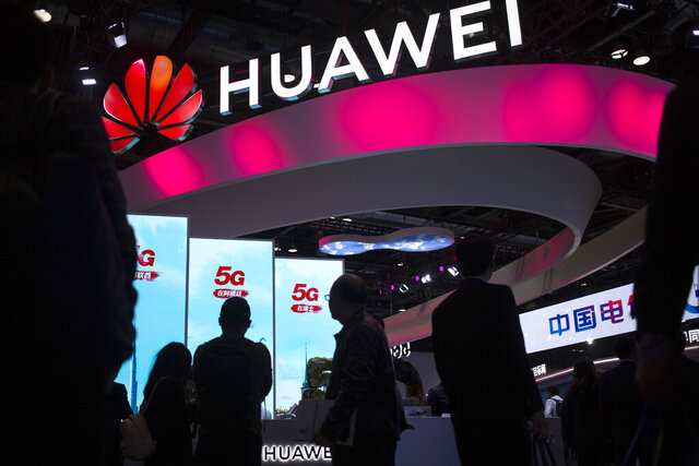 FILE - In this Oct. 31, 2019, file photo, attendees walk past a display for 5G services from Chinese technology firm Huawei at the PT Expo in Beijing. Chinese tech giant Huawei says its 2019 sales rose 19.1% over a year earlier despite U.S. sanctions that hampered its smartphone and network equipment businesses. (AP Photo/Mark Schiefelbein, File)