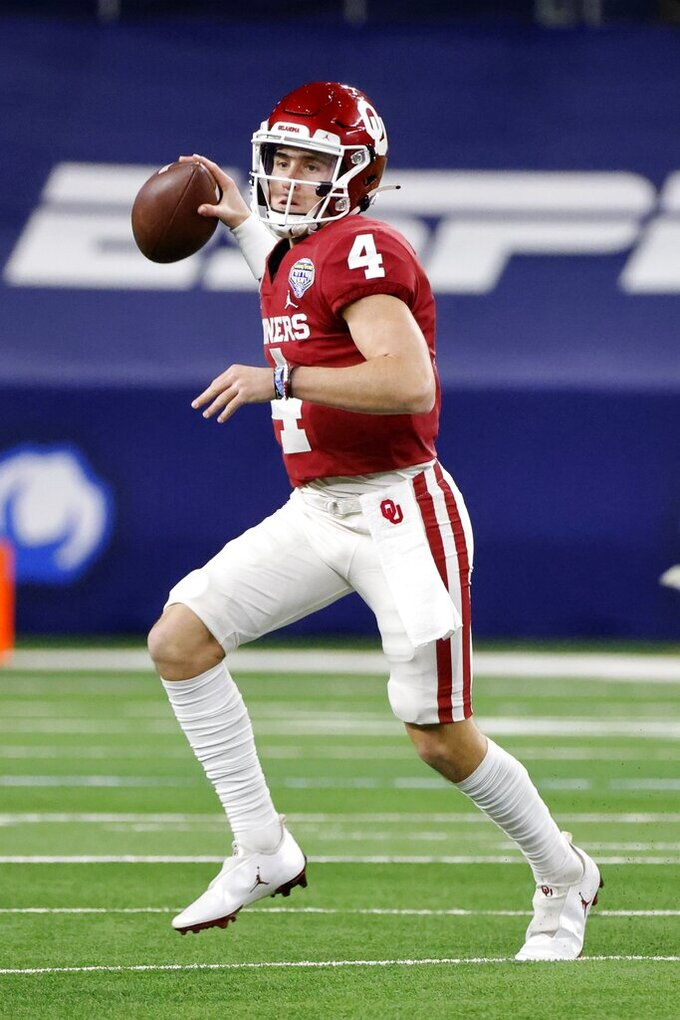 Oklahoma quarterback Chandler Morris (4) scrambles before throwing a pass during the second half of the team's Cotton Bowl NCAA college football game against Florida in Arlington, Texas, Wednesday, Dec. 30, 2020. (AP Photo/Michael Ainsworth)