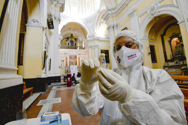 A medical operator prepares to perform COVID-19 test swabs in the Church of San Severo Outside the Walls, in the heart of Naples, Italy, Wednesday, Nov. 18, 2020. An initiative of