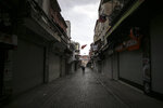 """People walk in Eminonu market, an area usually packed with shop goers, but currently nearly deserted due to the strict lockdown to help curb the spread of the coronavirus, in Istanbul, Saturday, May 8, 2021. The """"full lockdown,"""" which began in late April and will last until May 17 came amid a huge surge in infections.  (AP Photo/Emrah Gurel)"""