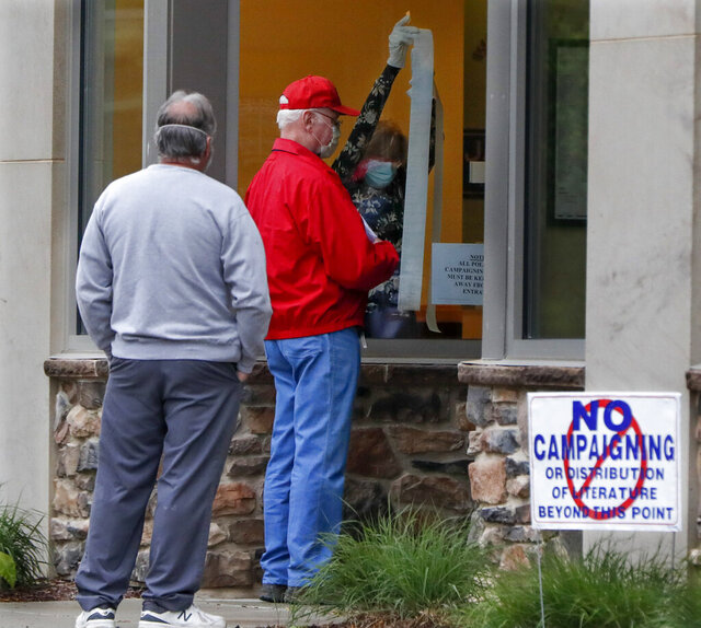 People wait outside as a poll worker prepares the voting place before the polls open for the Pennsylvania Primary election, Tuesday, June 2, 2020, in Zelienople, Pa. (AP Photo/Keith Srakocic)