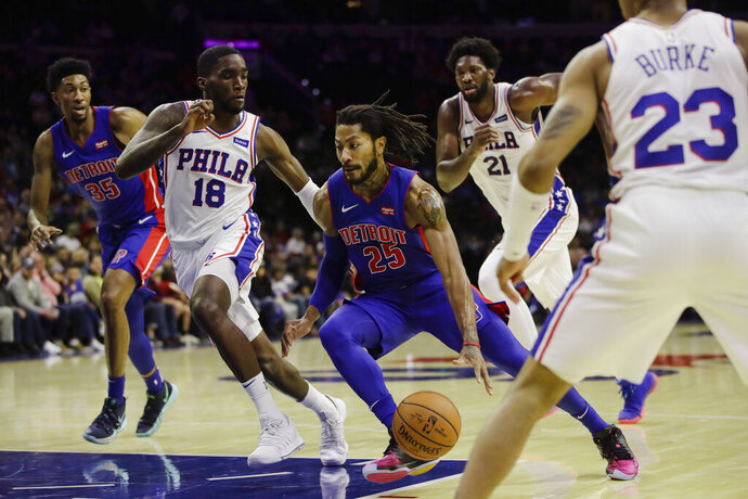 Detroit Pistons' Derrick Rose (25) drives as Philadelphia 76ers' Shake Milton (18), Joel Embiid (21) and Trey Burke (23) defend and 76ers' Christian Wood (35) watches during the first half of an NBA preseason basketball game Tuesday, Oct. 15, 2019, in Philadelphia. (AP Photo/Matt Rourke)