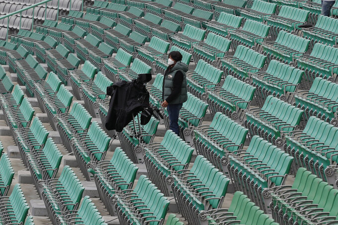 A TV camera man works near empty seats before the start of a baseball game between Hanwha Eagles and SK Wyverns in Incheon, South Korea, Tuesday, May 5, 2020. Cheerleaders danced beneath rows of empty seats and umpires wore protective masks as a new baseball season began in South Korea. After a weeks-long delay because of the coronavirus pandemic, a hushed atmosphere allowed for sounds like the ball hitting the catcher's mitt and bats smacking the ball for a single or double to echo around the stadium. (AP Photo/Lee Jin-man)
