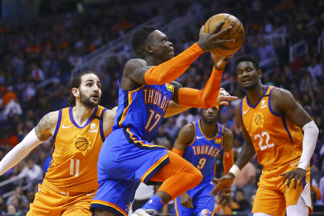 FILE - Oklahoma City Thunder guard Dennis Schroder (17) drives past Phoenix Suns guard Ricky Rubio (11) as Suns center Deandre Ayton (22) and Thunder center Nerlens Noel (9) watch during the first half of an NBA basketball game in Phoenix, in this Friday, Jan. 31, 2020, file photo. Teams may begin making trades Monday, according to a memo sent to teams and obtained early Sunday, Nov. 15, 2020, by The Associated Press. And the first deal known to be tentatively agreed upon would send guard Dennis Schröder from Oklahoma City to the champion Los Angeles Lakers for Danny Green and the No. 28 pick in Wednesday's draft, a person with knowledge of that agreement told the AP. (AP Photo/Ross D. Franklin, File)