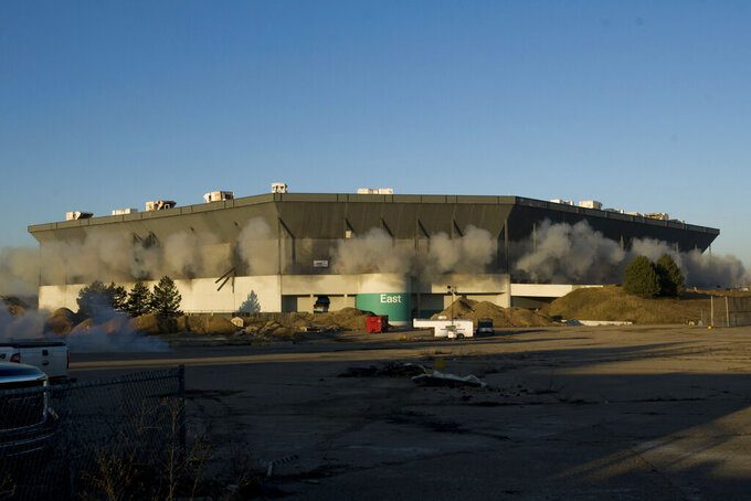 FILE - In this Dec. 3, 2017, file photo, detonations can be seen during an attempted implosion of the Silverdome, in Pontiac, Michigan. Online retail giant Amazon has proposed using the site of the former home of the Detroit Lions as a distribution center in a $250 million project that could bring 1,500 jobs. Details of plans for the Pontiac Silverdome site in suburban Detroit were made public Wednesday night, Sept. 18, 2019. (David Guralnick/Detroit News via AP, File)