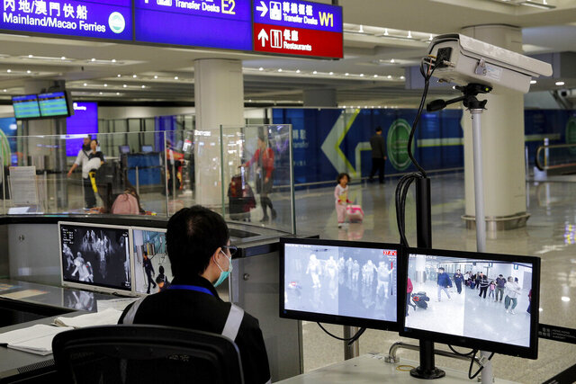 FILE - In this Jan. 4, 2020, file photo, a health surveillance officer monitors passengers arriving at the Hong Kong International airport in Hong Kong. On Friday, Jan. 17, 2020, the U.S. Centers for Disease Control and Prevention officials said they will begin screening airline passengers at three U.S. airports who traveled from Wuhan in central China, for a new illness that has prompted worries about a new international outbreak. (AP Photo/Andy Wong, File)