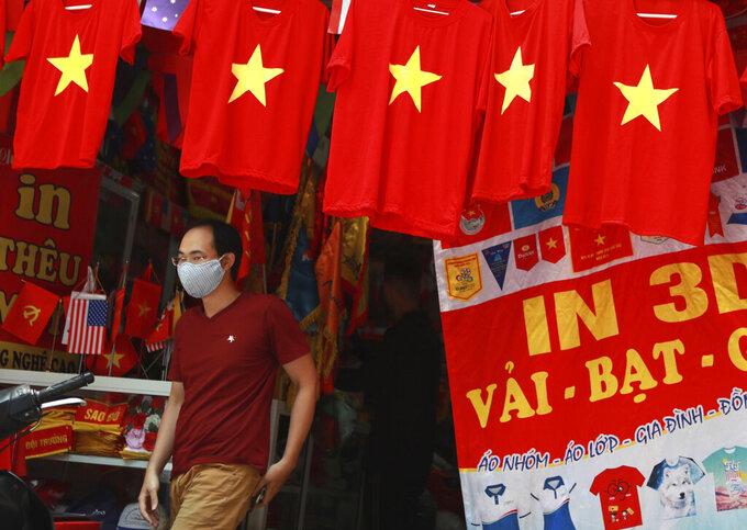 A man walks past a row of T-shirts printed with Vietnamese flags in Hanoi, Vietnam on Thursday, Jul.30, 2020. For 99 days, Vietnam seemed to have defeated the coronavirus, but now a new outbreak in the city of Da Nang has grown to over 40 cases in six cities and authorities are beginning to reimpose broader restrictions. (AP Photo/Hau Dinh)