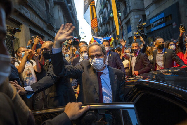 Catalonia's outgoing regional president, Quim Torra, waves to the crowd as he leaves the Generalitat Palace in Barcelona, Spain on Monday, Sept. 28, 2020. Spain's Supreme Court has barred Catalonia's regional president from his office for refusing to remove a banner calling for the release of separatist leaders from prison that was displayed on a public building ahead of the 2019 general election (AP Photo/Emilio Morenatti)