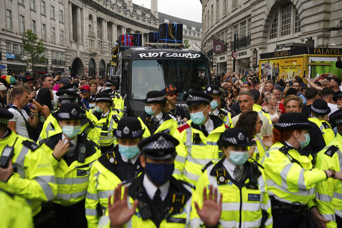 Police precede protesters, leading them along Regent Street in central London during a #FreedomToDance march organised by Save Our Scene, calling for easing of restrictions for music events, in London, Sunday June 27, 2021.  Large crowds gathered in central London to protest over what they called the government's perceived disregard for the live music industry throughout the coronavirus pandemic. (Aaron Chown/PA via AP)