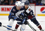 Winnipeg Jets center Jack Roslovic, front, wins a race to the puck in front of Colorado Avalanche center Tyson Jost during the second period of an NHL hockey game Tuesday, Dec. 31, 2019, in Denver. (AP Photo/David Zalubowski)
