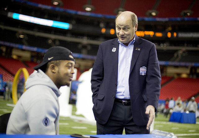 FILE - In this Dec. 29, 2016, file photo, Gary Stokan, Peach Bowl president and CEO, right, talks with Washington's Chico McClatcher during media day for the Peach Bowl NCAA college football game in Atlanta. Stokan is considering multiple contingency plans for three kickoff games planned in Atlanta, but there is one bottom line: If it's not safe for fans, the three games, Florida State-West Virginia, Georgia-Virginia and North Carolina-Auburn, won't be played at Mercedes-Benz Stadium. (AP Photo/David Goldman, File)