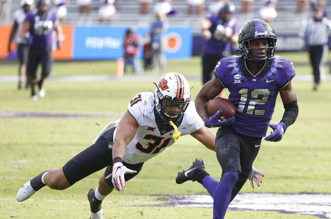 TCU wide receiver Derius Davis (12) gets past Oklahoma State safety Kolby Harvell-Peel (31) to score a touchdown during the second half of an NCAA college football game Saturday, Dec. 5, 2020, in Fort Worth, Texas. (AP Photo/Ron Jenkins)