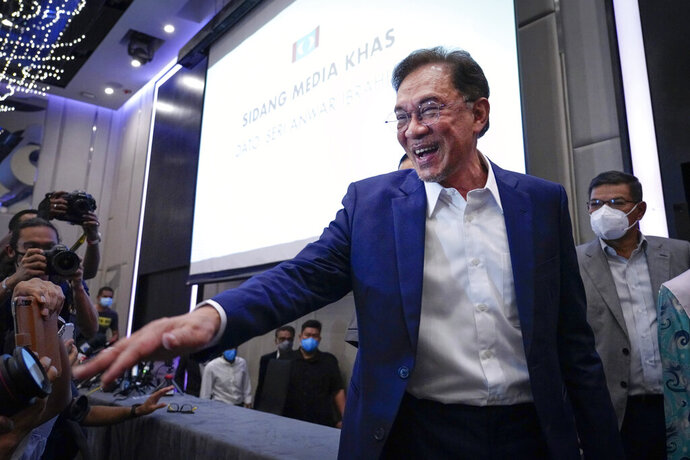 "Malaysia's opposition leader Anwar Ibrahim gestures as he leaves after a press conference in Kuala Lumpur, Wednesday, Sept. 23, 2020. Anwar said he has secured a majority in parliament to form a new government that is ""strong, stable and formidable."