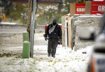 A pedestrian walks along West Main Street at the gap during the first snowfall of the winter season on Thursday, Oct. 10, 2019, in Rapid City, S.D. A powerful winterlike storm moving through the Great Plains was closing schools and causing travel headaches in several states, authorities said Thursday.  (Adam Fondren/Rapid City Journal via AP)