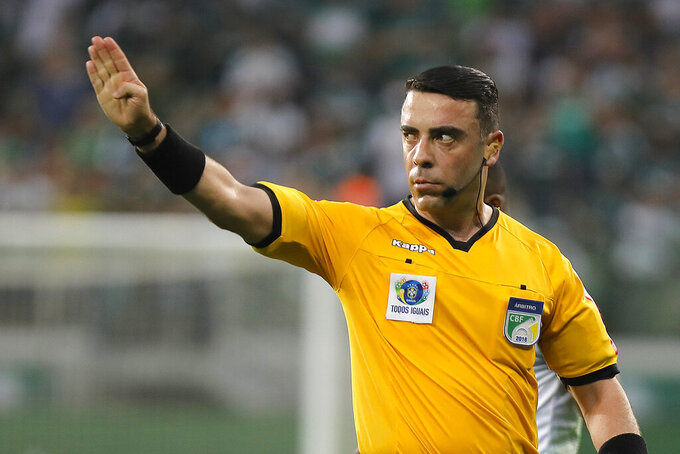 Brazilian referee Igor Benevenuto works during the Brazilian championship soccer game between Palmeiras and Bahia in Sao Paulo, Brazil, Nov.8, 2019. When the coronavirus pandemic forced Brazilian soccer to take a break, Benevenuto took one of the few jobs that were still in high demand in his countryside city of Sete Lagoas, as a nurse at a public hospital filled with COVID-19 patients. (Daniel Vorley/AGIF via AP)