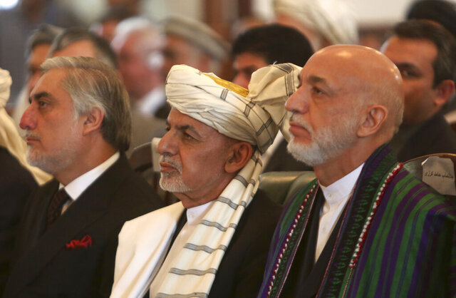 FILE - In this Sept. 29, 2020, Afghan President Ashraf Ghani, center, former President Hamid Karzai, right, and Chief Executive Abdullah Abdullah, left, watch the live broadcast of Gulbuddin Hekmatyar after the signing of a peace treaty at the presidential palace in Kabul, Afghanistan. Officials on both sides of Afghanistan's protracted conflict say efforts are ramping up for the start of intra-Afghan negotiations, a critical next step to a U.S. negotiated peace deal with the Taliban. (AP Photo/Rahmat Gul, File)