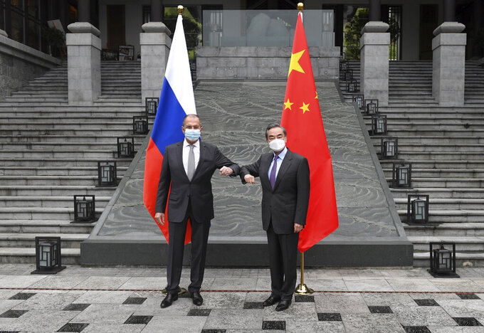 In this photo released by China's Xinhua News Agency, Russian Foreign Minister Sergei Lavrov, left, meets with Chinese Foreign Minister Wang Yi in Guilin in southern China's Guangxi Zhuang Autonomous Region, Monday, March 22, 2021. (Lu Boan/Xinhua via AP)