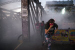 Anti-government demonstrators run from tear gas fired by police during protests against economic inequality in Santiago, Chile, Wednesday, Oct. 30, 2019. Chilean President Sebastian Pinera cancelled two major international summits after nearly two weeks of nationwide protests that have left at least 20 dead and damaged businesses and infrastructure around the country. (AP Photo/Rodrigo Abd)