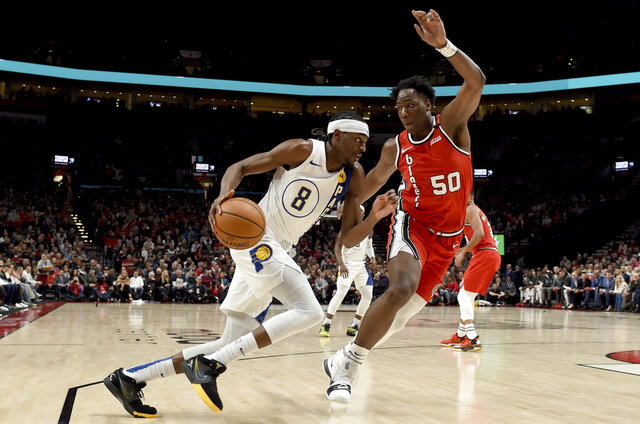 Indiana Pacers forward Justin Holiday, left, drives to the basket on Portland Trail Blazers forward Caleb Swanigan, right, during the first half of an NBA basketball game in Portland, Ore., Sunday, Jan. 26, 2020. (AP Photo/Steve Dykes)