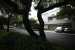 Cars sit outside the home of former first lady Angelica Rivera, in the Lomas de Chapultepec neighborhood of Mexico City, Friday, July 19, 2019. A gang of at least seven gunmen burst into the Mexico City home of the former first lady and forced employees to hand over valuables. (AP Photo/Rebecca Blackwell)