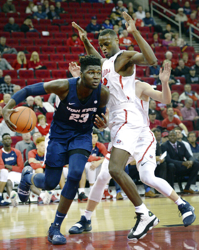 Utah State's Neemias Queta, left, dribbles around around Fresno State's Nate Grimes during an NCAA college basketball game in Fresno, Calif., on Tuesday, Feb. 5, 2019. (Craig Kohlruss/The Fresno Bee via AP)