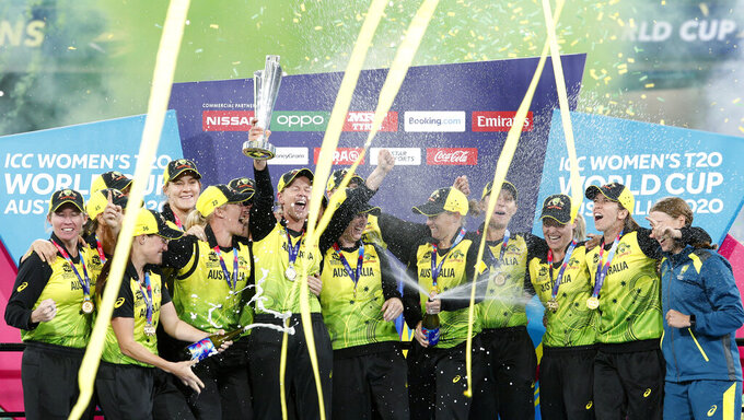 FILE - In this March 8, 2020, file photo, Australian players celebrate their win over India in the Women's T20 World Cup cricket final match in Melbourne. A three-match one-day international series between the Australia and India women's cricket teams has been postponed indefinitely and likely won't be played until 2022. (AP Photo/Asanka Ratnayake, File)