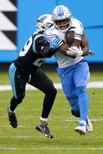 Detroit Lions running back Kerryon Johnson, right, is tackled by Carolina Panthers cornerback Corn Elder during the second half of an NFL football game Sunday, Nov. 22, 2020, in Charlotte, N.C. (AP Photo/Brian Blanco)