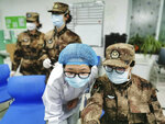 In this Jan. 26, 2020, photo released by Xinhua News Agency, a member of a military medical team takes over the work from a medical worker at Wuhan Jinyintan Hospital in Wuhan, central China's Hubei province. China on Monday expanded sweeping efforts to contain a viral disease by postponing the end of this week's Lunar New Year holiday to keep the public at home and avoid spreading infection. (Li Yun/Xinhua via AP)