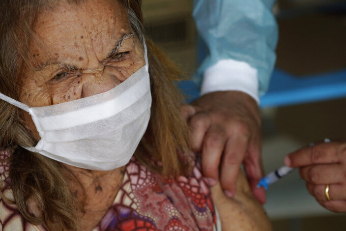 FILE - In this Feb. 18, 2021, file photo, a senior receives her second dose of China's Sinovac CoronaVac vaccine, during a priority vaccination program for the elderly at the Bezerra de Menezes Asylum in Brasilia, Brazil. The global death toll from the coronavirus topped a staggering 3 million people Saturday, April 17, 2021, amid repeated setbacks in the worldwide vaccination campaign and a deepening crisis in places such as Brazil, India and France. (AP Photo/Eraldo Peres, File)