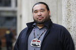 Makah Tribal Council Member Patrick DePoe poses for a photo before a federal court hearing to help determine whether his small American Indian tribe can once again hunt whales, Thursday, Nov. 14, 2019, in Seattle. The symbol he wears is from the tribes flag, and includes bird and whale symbols. The Makah Tribe, from the northwest corner of Washington state, conducted its last legal hunt in 1999, when its crew harpooned a gray whale from a cedar canoe. (AP Photo/Elaine Thompson)