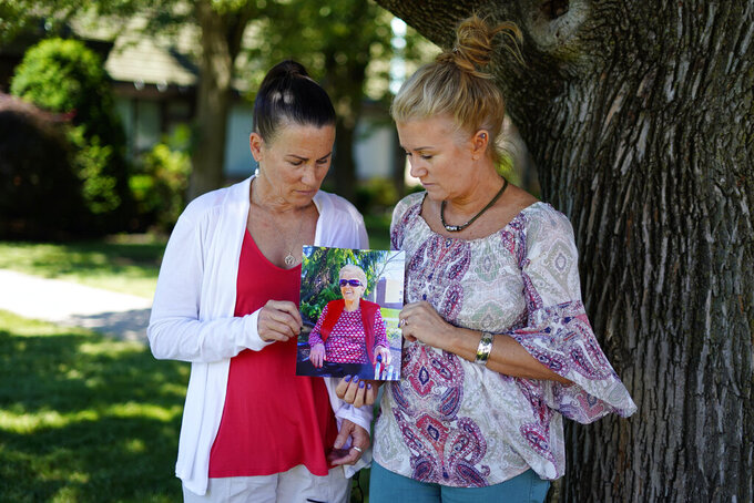 """Angela Ermold, right, and her sister, Denise Gracely, hold a photo of their mother, Marian Rauenzahn, Thursday, June 17, 2021, in Fleetwood, Pa. Pandemic restrictions are falling away almost everywhere — except inside many of America's nursing homes. """"They have protected them to death,"""" said Gracely. (AP Photo/Matt Slocum)"""