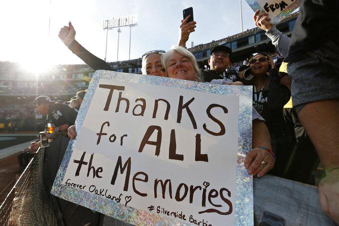 Aficionados de los Raiders sostienen un letrero en la segunda mitad del juego de loa Raiders de Oakland ante los Jaguars de Jackonsville en el último partido en el Oakland Coliseum el domingo 15 de diciembre del 2019.  (AP Photo/D. Ross Cameron)
