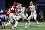 Florida quarterback Kyle Trask, right, drops back to throw as offensive lineman Ian McIver (61) blocks as Oklahoma defensive lineman Isaiah Thomas (95) watches the quarterback during the first half of the Cotton Bowl NCAA college football game in Arlington, Texas, Wednesday, Dec. 30, 2020. (AP Photo/Ron Jenkins)