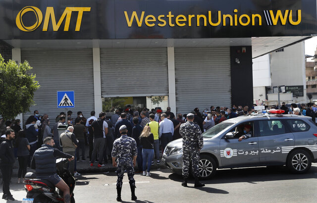 Lebanese citizens queue outside a Western Union shop to receive their money transfer in U.S. dollar currency, after the Central Bank circular issued this week, money transfer houses and banks are required to convert foreign currency transfers and cash withdrawals from foreign currency bank accounts to local currency at a market rate, in Beirut, Lebanon, Thursday, April 23, 2020. Lebanon's currency continued its downward spiral before the dollar on Thursday, reaching a new low amid financial turmoil in the crisis-hit country. (AP Photo/Hussein Malla)